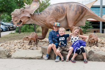 Liske kids with three dinosaurs at Drumheller Royal Tyrell Museum
