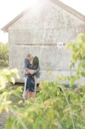 Couple kissing with sun flare on the farm