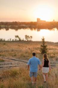 Couple walking hand in hand through the long grass at sunset