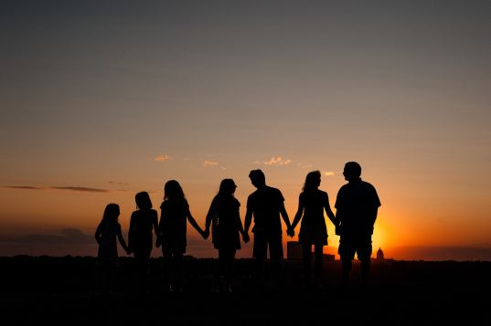 Family holding hands at sunset overlooking the city