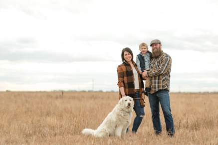 Family with their white dog in harvested field