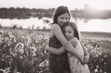 Sisters hugging together at sunset in black and white