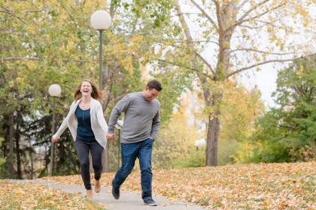 Couple walking through Wascana Park holding hands