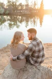 Engaged couple overlooking the water at sunset in Wascana Park