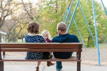 Family cuddles on the bench at the playground in Wascana Park