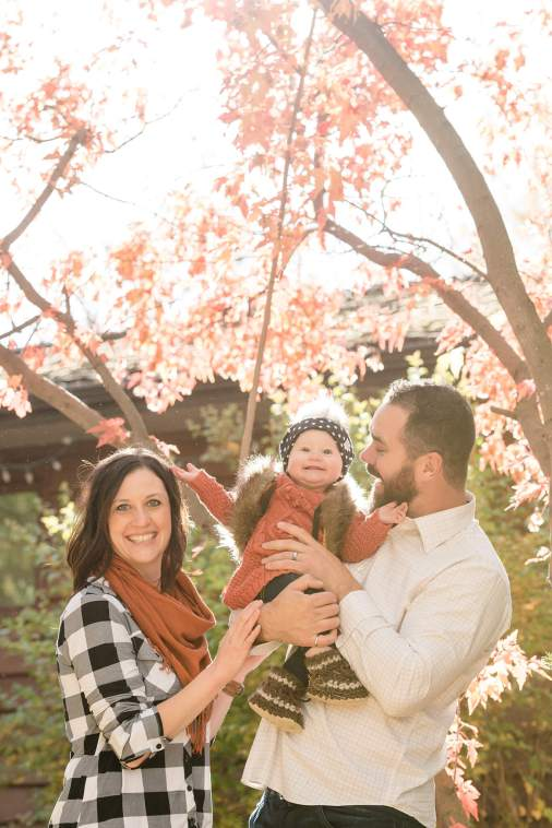 Family of three under red leafed tree