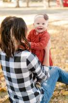 Little girl smiling with her mother in plaid shirt