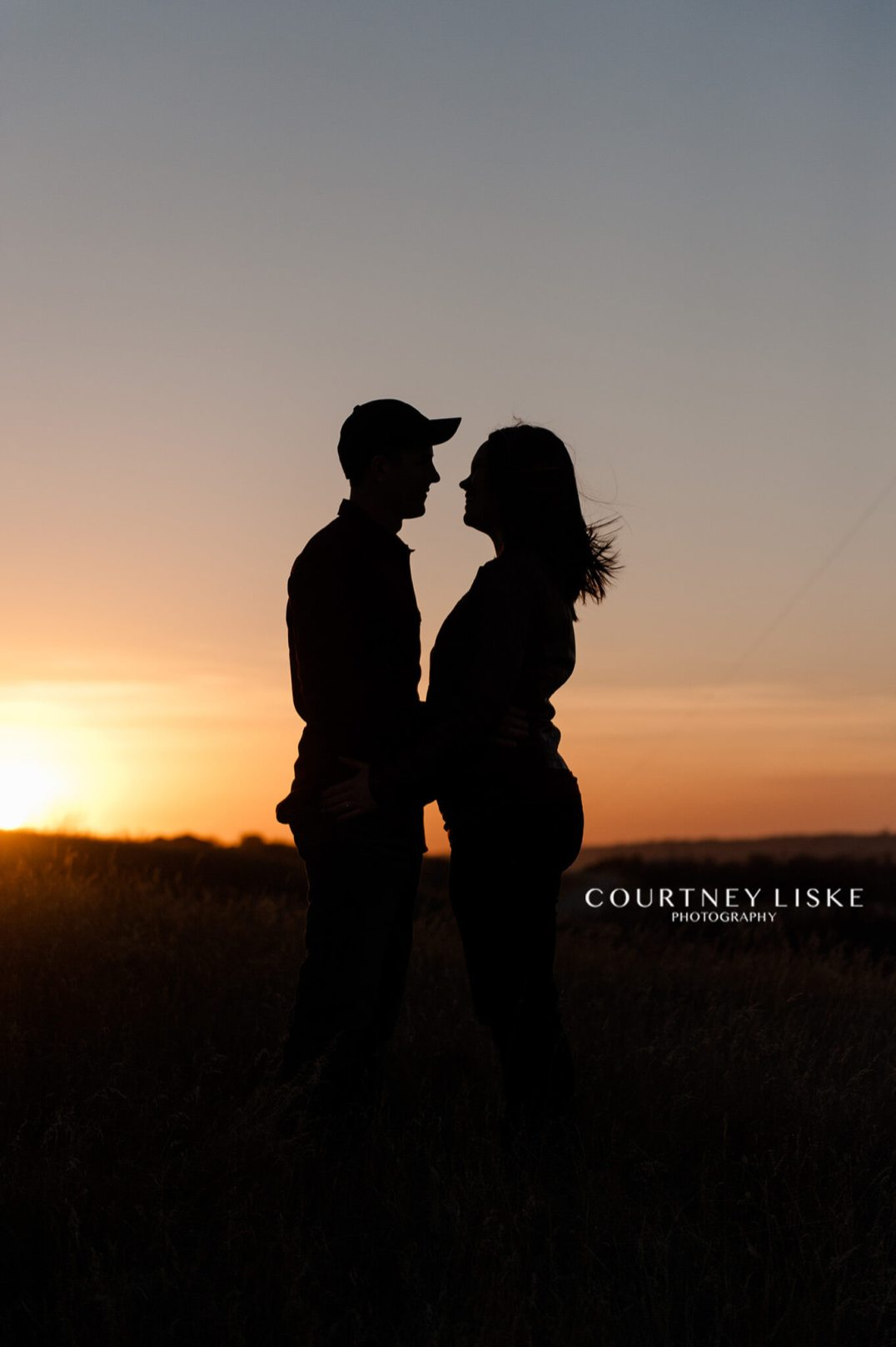 Man and woman standing in field at sunset