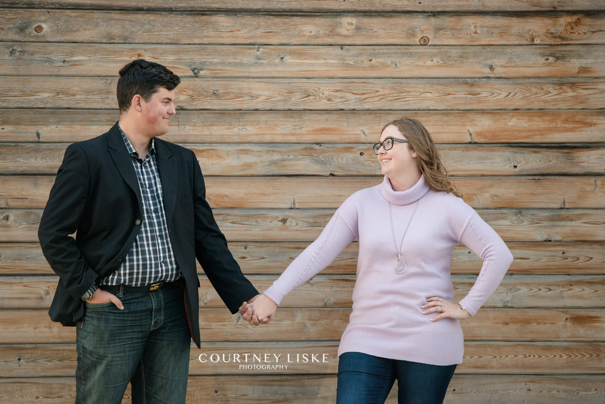 Couple stand holding hands against shiplap barnwood wall