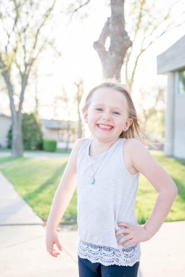 Little girl in grey tank top smiles in the sunshine