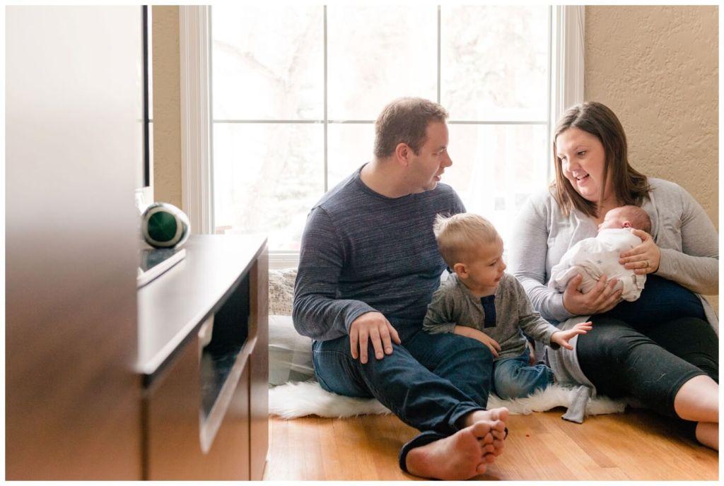 Regina Family Photography - Jensen Newborn - Keltie-Josh-Kayden - In home Family Session - Family seated on hardwood floor