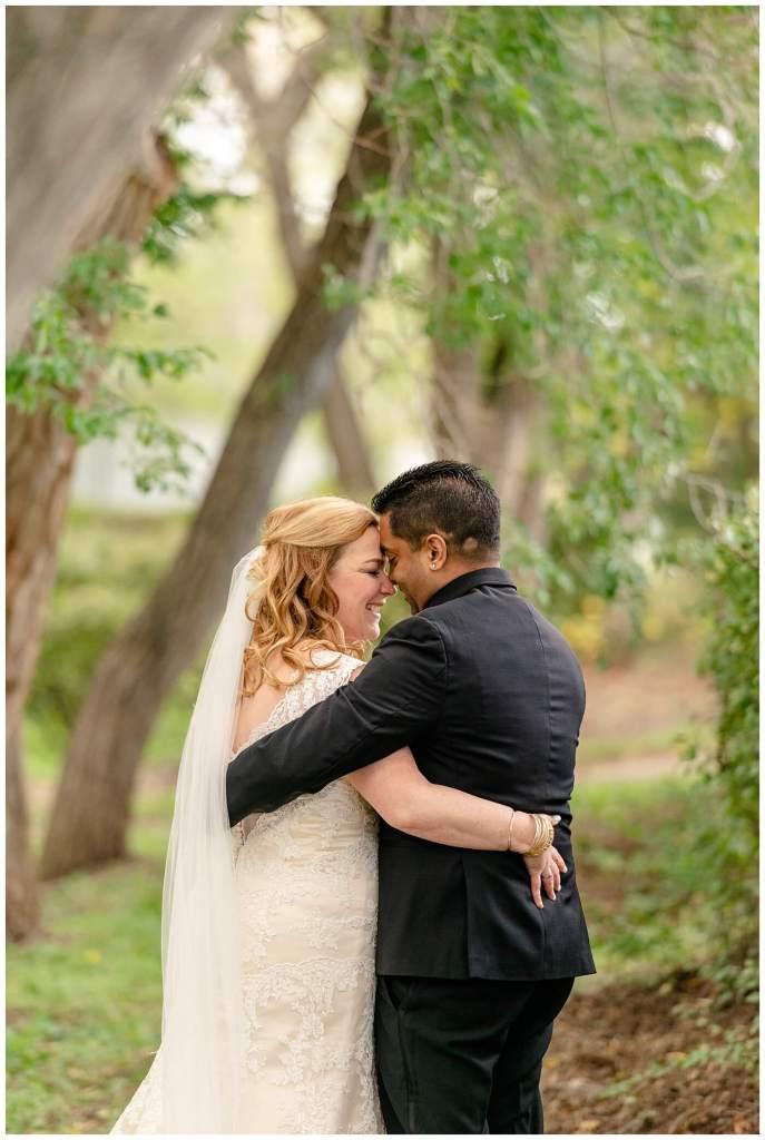 Regina Wedding Photography - Nishant - Corrina - Bridal Portraits - Regina Kiwanis Park - Bride & Groom take a moment to cuddle amongst the trees