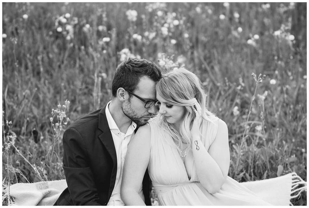 Regina Wedding Photographer - Natural Light Engagement Session in Douglas Park Regina - Couple sit on a blanket in tall grass at sunset