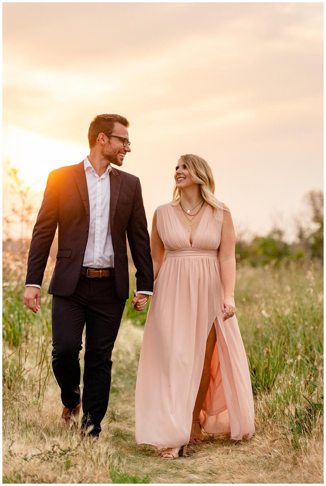 Regina Wedding Photographer - Natural Light Engagement Session in Douglas Park Regina - Couple walk along the path at sunset inside the Wascana Habitat Conservation Area