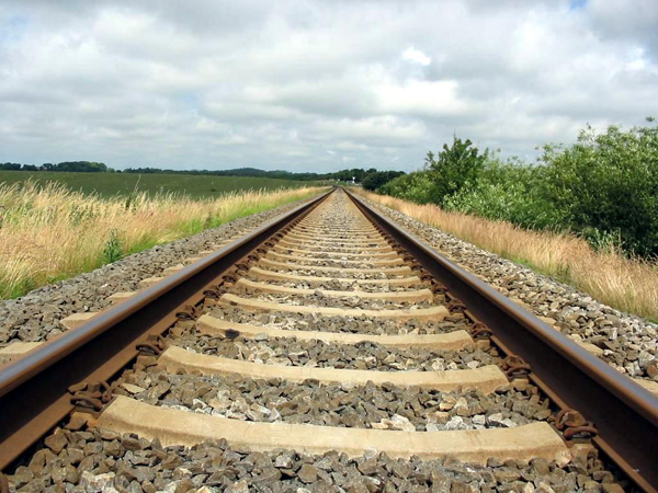 Railroad tracks disappearing into the distance. Shown with cement ties and stone bedding, with fields and bushes to the sides.