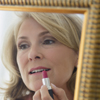 Blond adult woman, shown in a mirror, putting on lipstick.