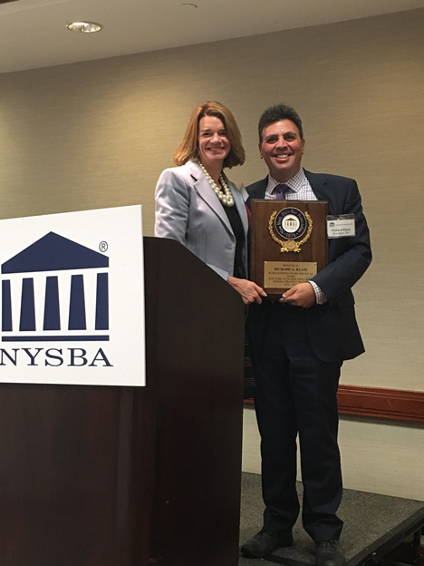 Emily Franchina poses with Richard Klass for a photo as he is awarded plaque for his service as Chair, New York State Bar Association, General Practice Section 2014-2015.