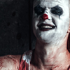 Somewhat frightening staged photo of a man with clown makeup, sitting on the ground, holding a hatchet, with blood on his shirt. Illustrates a case study about an order of attachment