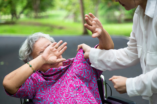 Woman with white hair and pink smock in a wheelchair, attendant in white coat grabbing her smock with another hand in a fist illustrating article by Richard Klass about nursing homes