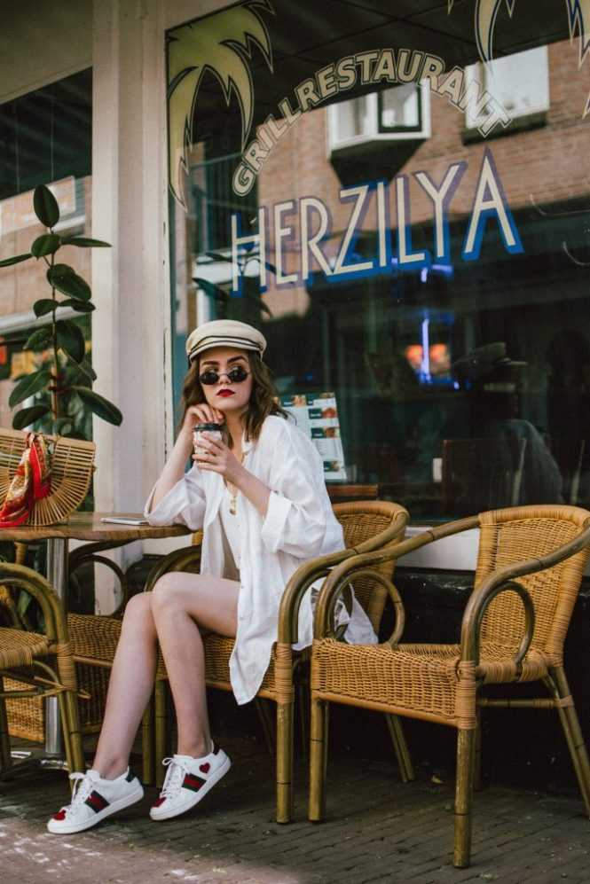 Striped linen shorts, white shirt, cami top, gucci sneakers, straw hat, cult gaia ark bag, cute summer outfit ideas 2018, andreea birsan, couturezilla, stradivarius beige linen shorts with belt, chain belt, la femme chain belt, straw baker boy hat, gucci ace heart embroidered white leather sneakers, white kicks, gucci trainers with hearts, gucci sneakers, the best white sneakers for women, females sneakers, straw newsboy hat, natural straw hat, small oval vintage sunglasses, vintage sunnies, micro sunglasses trend, wavy hair, schiedeam, rotterdam, the netherlands, holland, what to do in schiedam, white cami top, the best cami top, camisole top, blouse, white linen oversized shirt, boyfriend fit white shirt, linen shirt, button up shirt, how to wear shirts in summer, white and beige outfit, what to wear with linen shorts, the best chain belt, chain belt trend, asos, what to wear when traveling, travel outfit, summer travel outfit, how to look Parisian chic, European summer street style inspiration for women 2017, pinterest chic outfit ideas for woman, summer outfit ideas, summer ootd inspiration, outfit of the day, ootd, fashion icon, style inspiration, fashionista, fashion inspiration, style inspo, what to wear in summer, how to look French, chic on a budget, zara outfit, mango, topshop, asos, river island, forever 21, urban outfitters, how to mix high end pieces with luxury ones, zara and Gucci,outfit alternatives for summer, tomboy chic, minimal outfit, tumblr girls photos, pictures, happy girl, women, smart casual outfits, the best outfit ideas 2017, what to wear when you don't feel inspired, summer in Europe, weekend attire, uniform, French women in summer, European outfit ideas 2017, minimal chic outfit, how to stand out, the best outfit ideas for summer, the sunglasses you have seen everywhere on Instagram, glasses, uk fashion blogger, united kingdom, uk fashion blog, fashion and travel blog, Europe, women with style, street style, summer fashion trends 2017, 