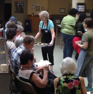 Food samples are handed out as part of a local outreach done in cooperation with a local garden project and a community cooking school. A dietitian speaks for the first half of the presentation, and then a chef demos healthy recipes.