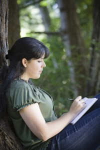 young woman writing in a journal outside