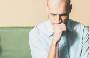 A man sitting distraught thinking about the effects of doing coke.