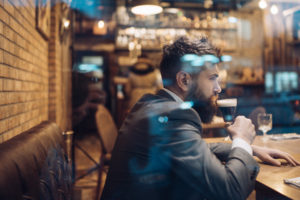 A businessman sitting in a bar drinking a glass of beer after work.
