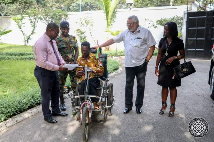 Former President Jerry John Rawlings suprises Emmanuel Ofoe, a physically-challenged street beggar