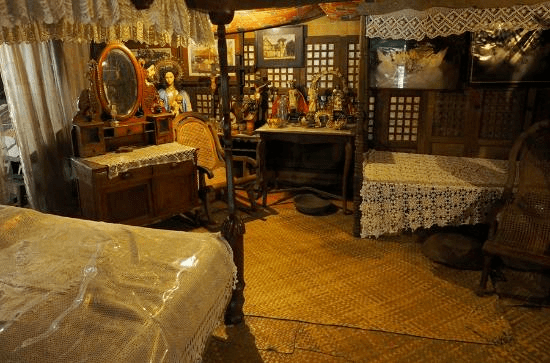 Old bed and furniture in one of the rooms at ancestral house