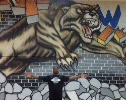 West Potomac coach David Houston III in front of the new mural