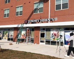 Ground level location of Jimmy John's with ladders in front of storefront.