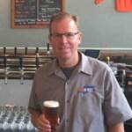 Jones holding beer at brewery