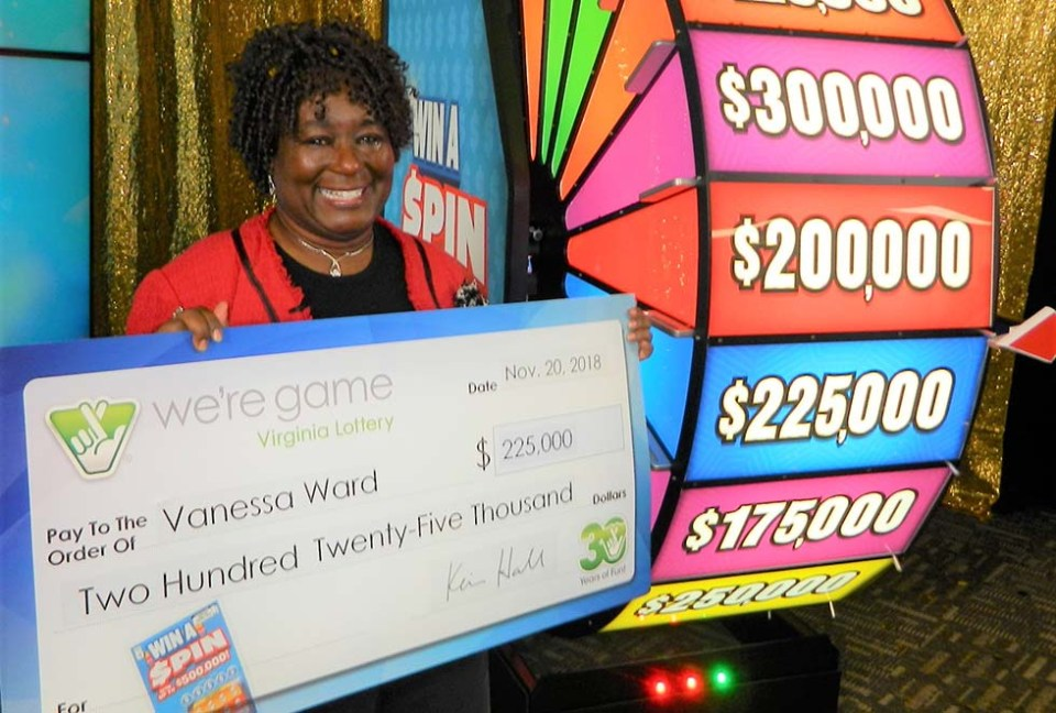 Woman holding large check in front of wheel seen in the game