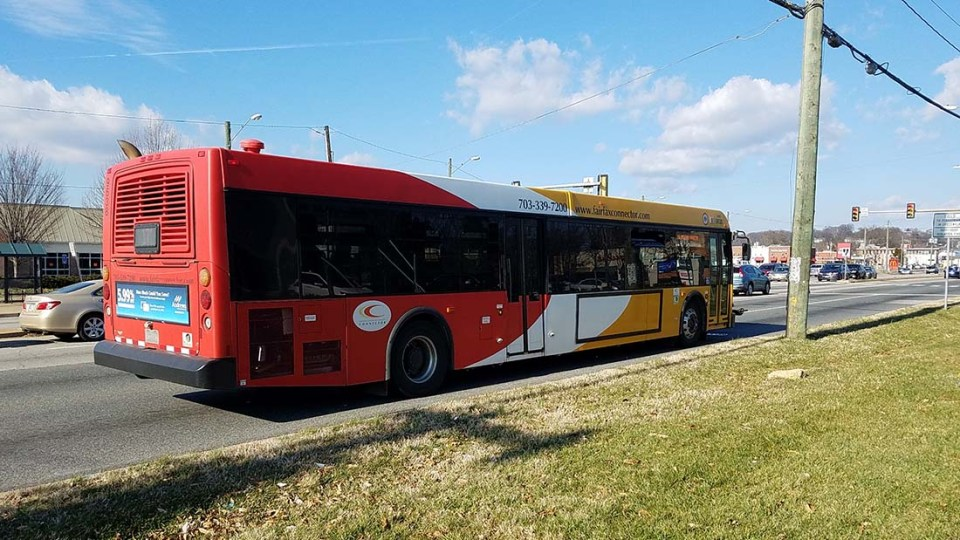 A Fairfax Connector bus driving north on a sunny day in Hybla Valley.