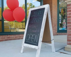 """Sign reading """"Now Open"""" in front of store"""