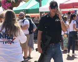 Man on cell phone while holding rifle at farmers market