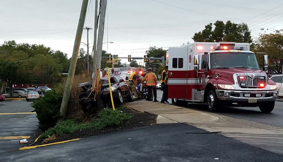 View of the crash scene, with broken pole and car on left and ambulance in roadway on right