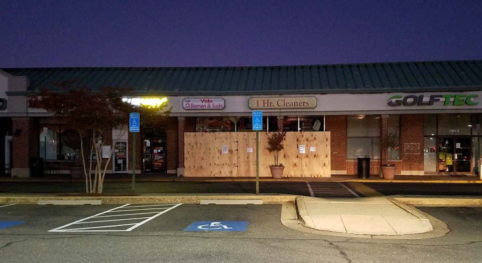 Front of business at night, with boarded up entrances of cleaners and Yido Ramen & Sushi in the middle