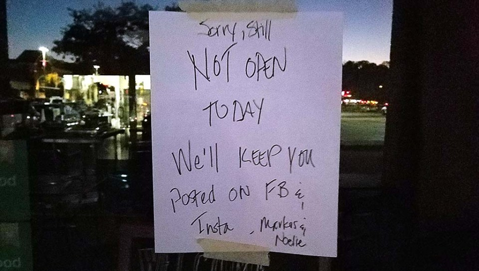"""A sign reading """"Sorry, still not open today. We'll keep you posted on FB & Insta"""""""