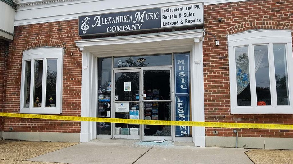 Storefront of Alexandria Music Company with tape in front of it and broken door