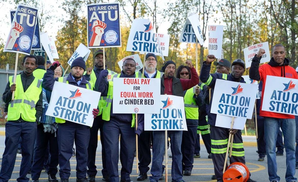 Workers holding signs that say ATU on Strike