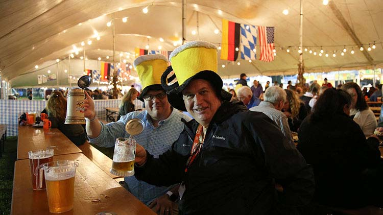 Two men holding beer steins at a bar