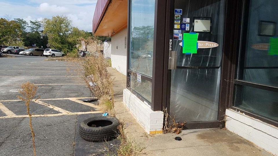 Tire next to entrance of Jerry's with weeds showing