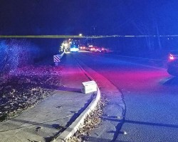 Crime scene tape in front of road with police vehicles in background on bridge