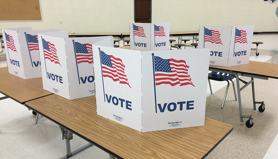 """Tables with """"Vote"""" written on cardboard that separates voting stations"""