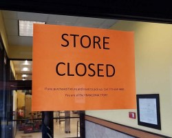 """Store Closed"" sign on door to Shoppers"