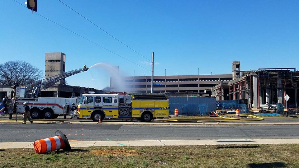 Firetrucks in front of South Alex site, one spraying water onto the rubble