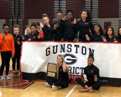 Hayfield gymnasts posing in front of and behind a Gunston District Champions banner