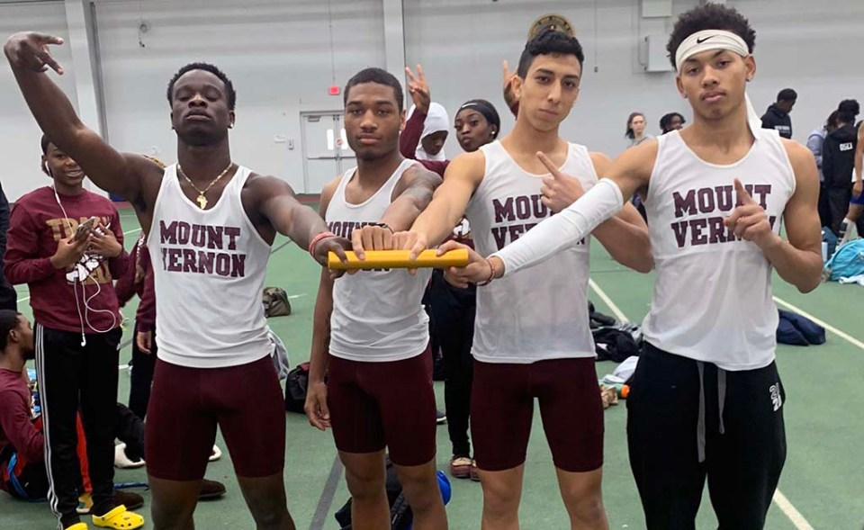 Relay team members posing for picture while holding baton